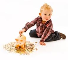 Kind wirft Geld in Sparschwein