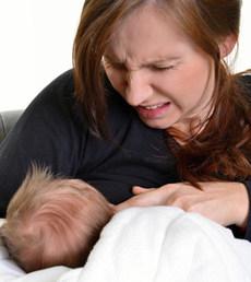 Stillende Mutter mit schmerzverzerrtem Gesicht