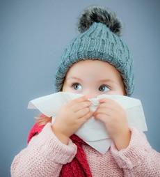 Baby putzt sich die Nase mit einem Tempo