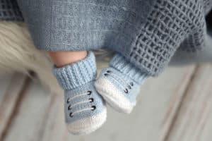 Baby trägt blaue selbst gehäkelte Chucks