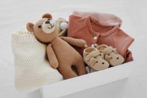 Babykleidung und Spielzeug in einer Box