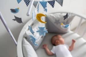 Baby schläft im Babybett und darüber hängt ein Mobile