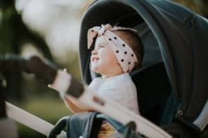 lachendes Baby sitzt draußen im Kinderwagen