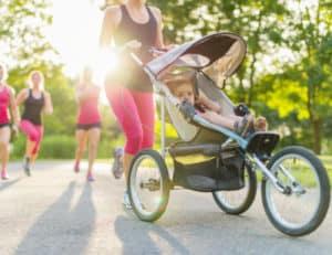 Mutter ist mit Kleinkind, das im Kinderwagen sitzt, joggen