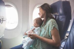 Mutter sitzt mit ihre Baby im Flugzeug