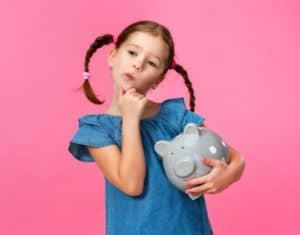 Kind hält großes Sparschwein im Arm