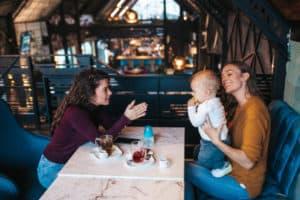 Mutter sitzt mit ihrem Kleinkind und einer Freundin im Café