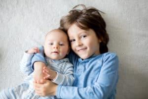 Ein Bruder umarmt seinen Neugeboren Burder