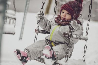 Kleinkind sitzt mit Schneeanzug in einer Schaukel