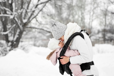 Baby im Schneeanzug ist mit Mutter spazieren